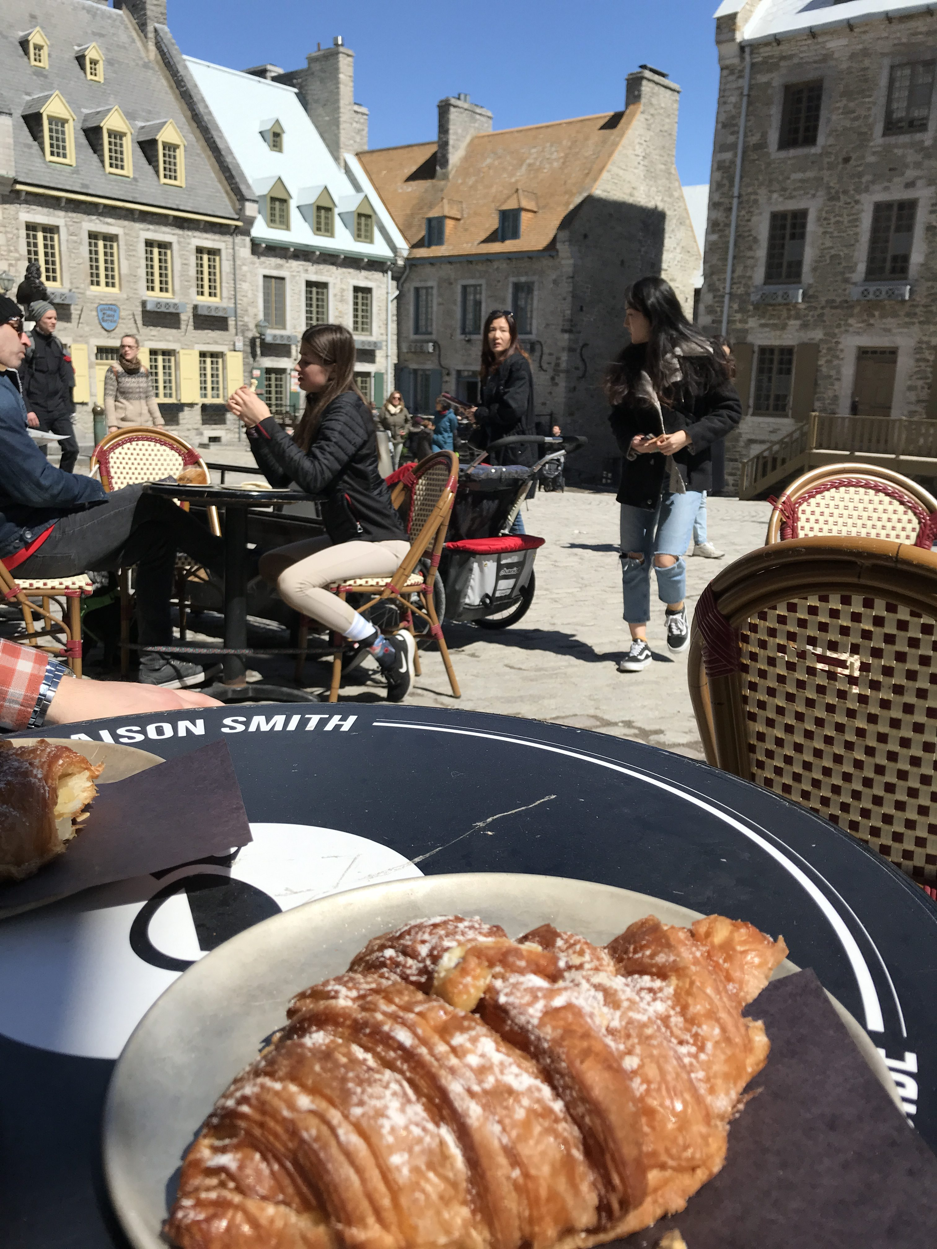 Eating a croissant at Place Royale in Quebec City.