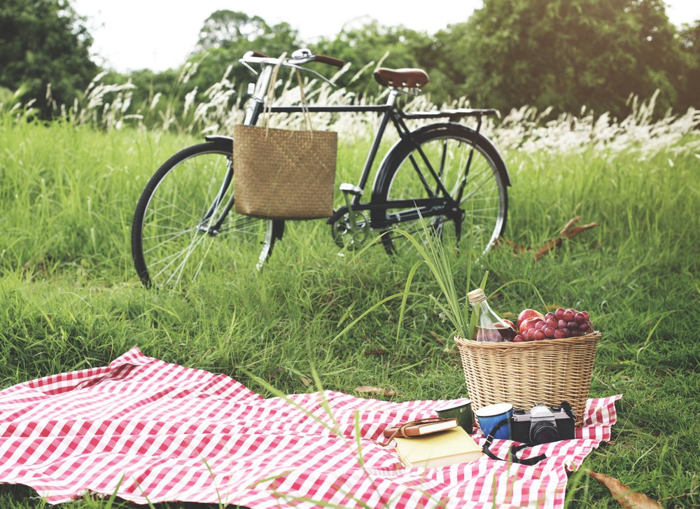 A blanket, picnic basket, and food in the grass - all essentials for a perfect picnic.