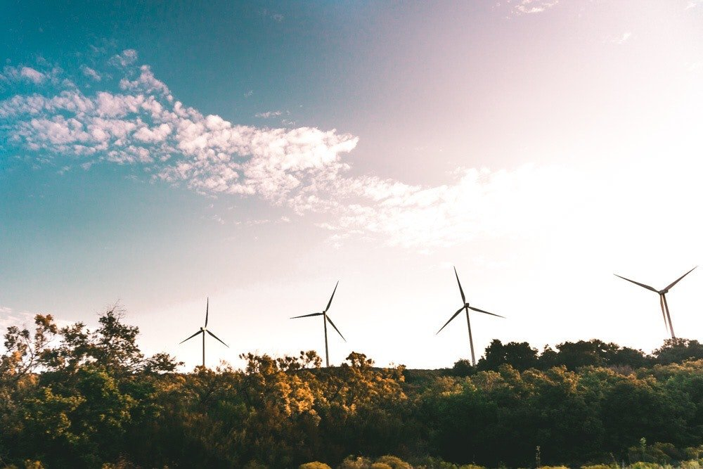 Windmills in an open field producing environmental sustainable energy.