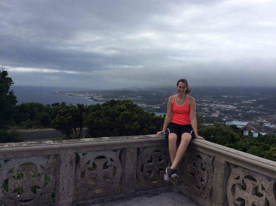 A woman sitting on a wall overlooking the city of Angra do Heroismo, Portugal.