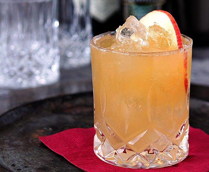 Gin apple cider ginger beer drink with an apple slice