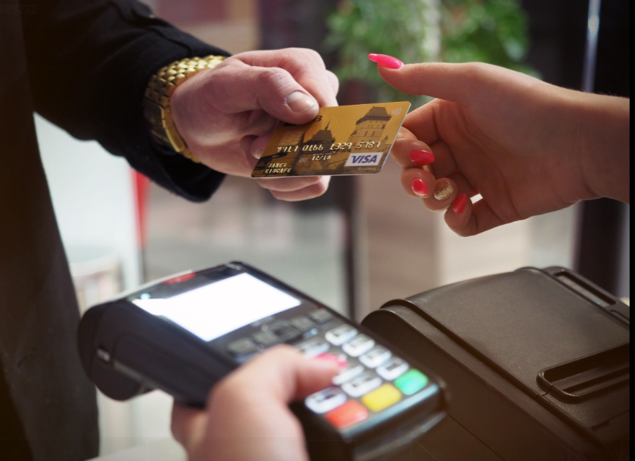 Man handing credit card to a woman - cash back on credit cards is an easy way to make extra money