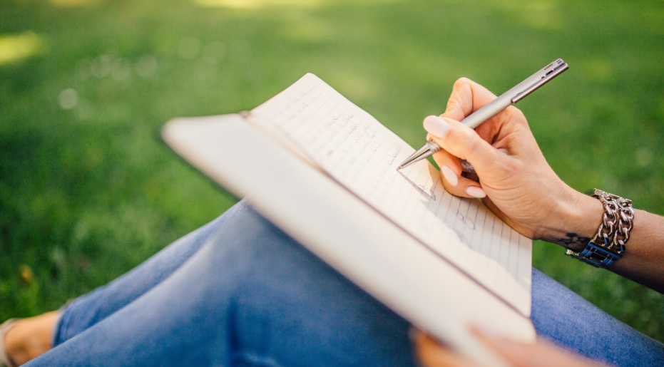 Woman writing in notebook on her lap