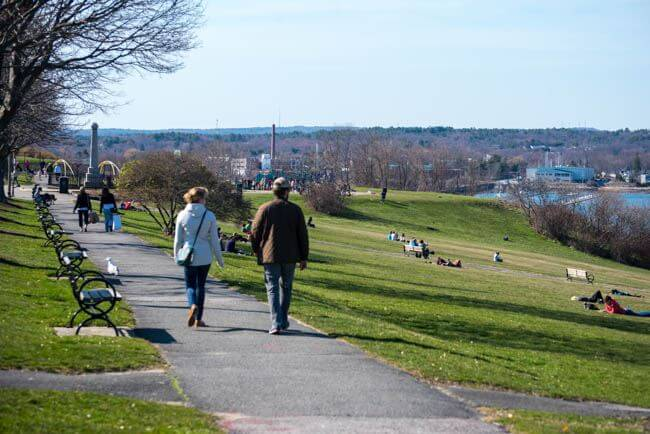 People enjoying the grass and walk along the Eastern Promenade in Portland, Maine.