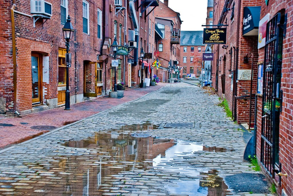 A cobblestone street with old brick buildings in the Old Port in Portland, Maine.