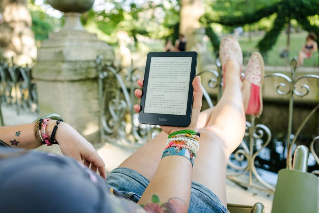 Woman reading an e-reader - selling ebooks is one of the best side hustles to start online in 2020