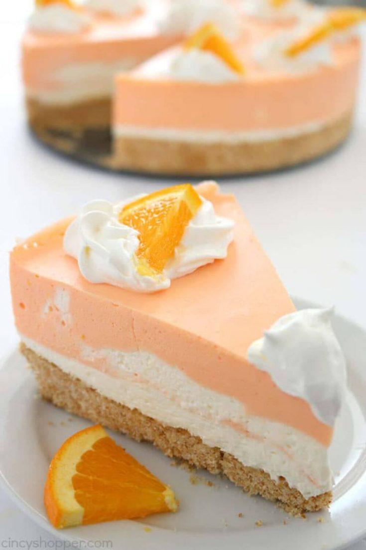 A layered slice of refreshing no-bake orange creamsicle cheesecake on a plate.