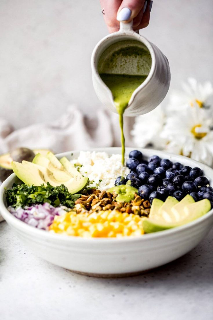 Green dressing being poured over a bowl of avocado blueberry quinoa salad.