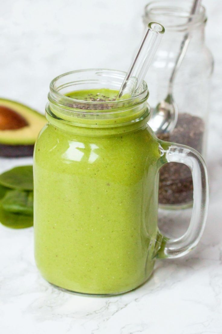 A mason jar full of green avocado smoothie with chia seeds.