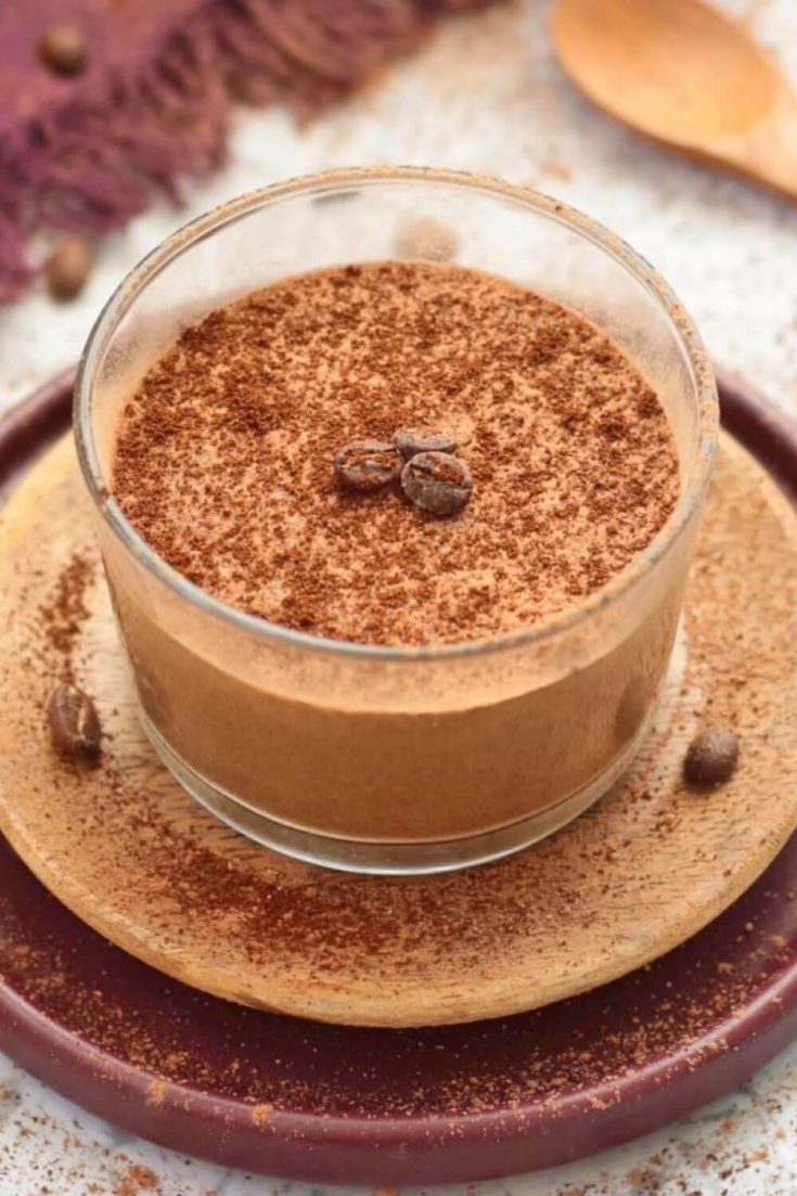A cup of yummy coffee mousse topped with cocoa powder and coffee beans.