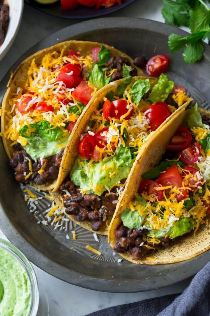 A platter of loaded black bean tacos topped with avocado lime cilantro crema.