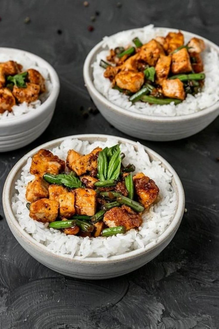 Three bowls of black pepper tofu with green beans over rice.