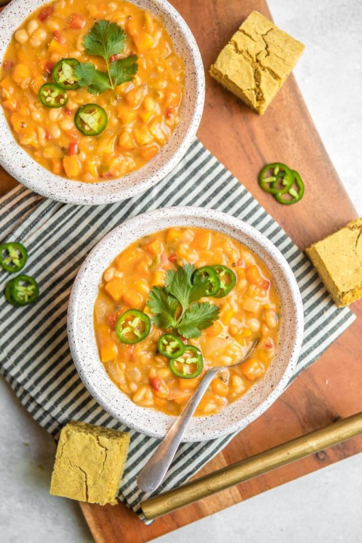 Two full bowls of butternut squash and white bean chili, topped with cilantro and jalapenos.