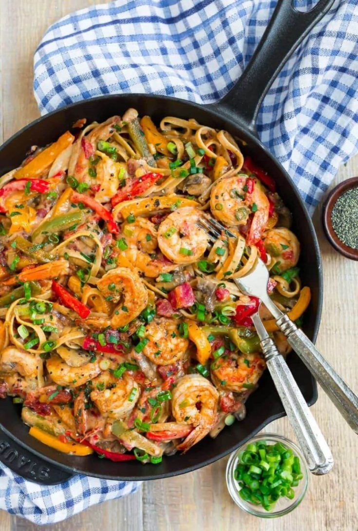 A full skillet of healthy cajun shrimp pasta with two forks in it.