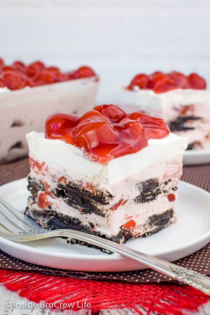 A layered piece of cherry oreo icebox cake on a plate.