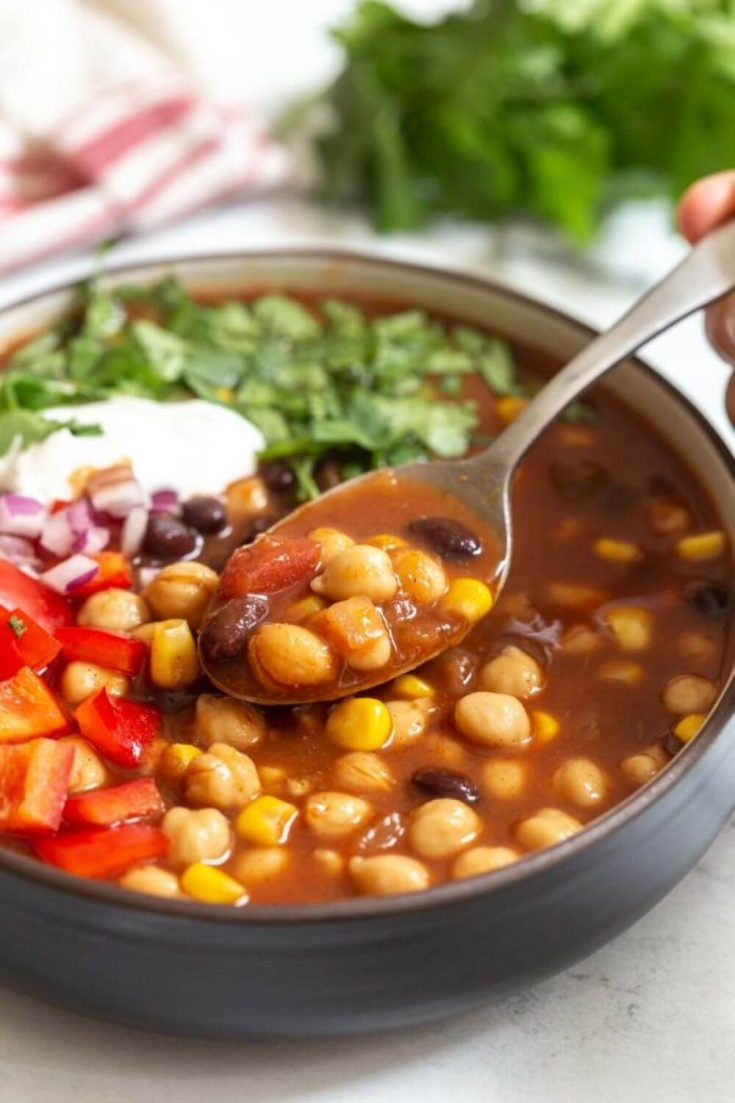A spoon in a large bowl of crockpot chickpea taco soup.