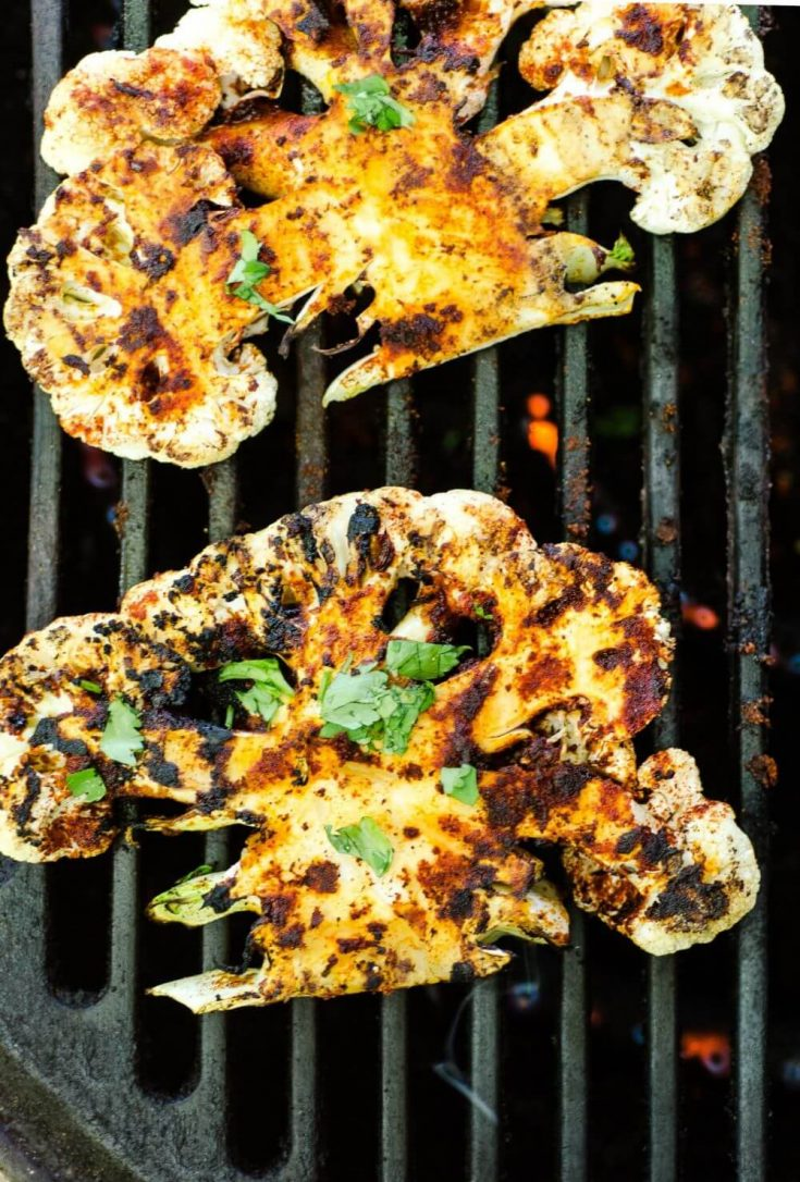 Two charred chipotle lime cauliflower steaks cooking on the grill.