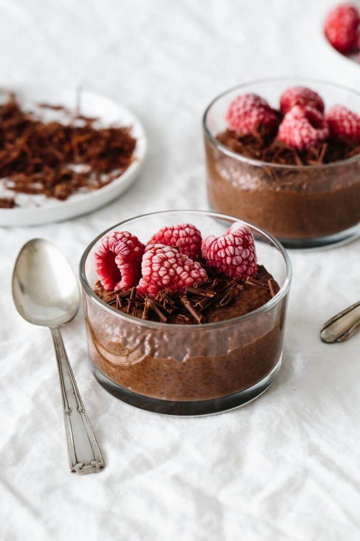 Two small dishes of chocolate chia pudding topped with raspberries.