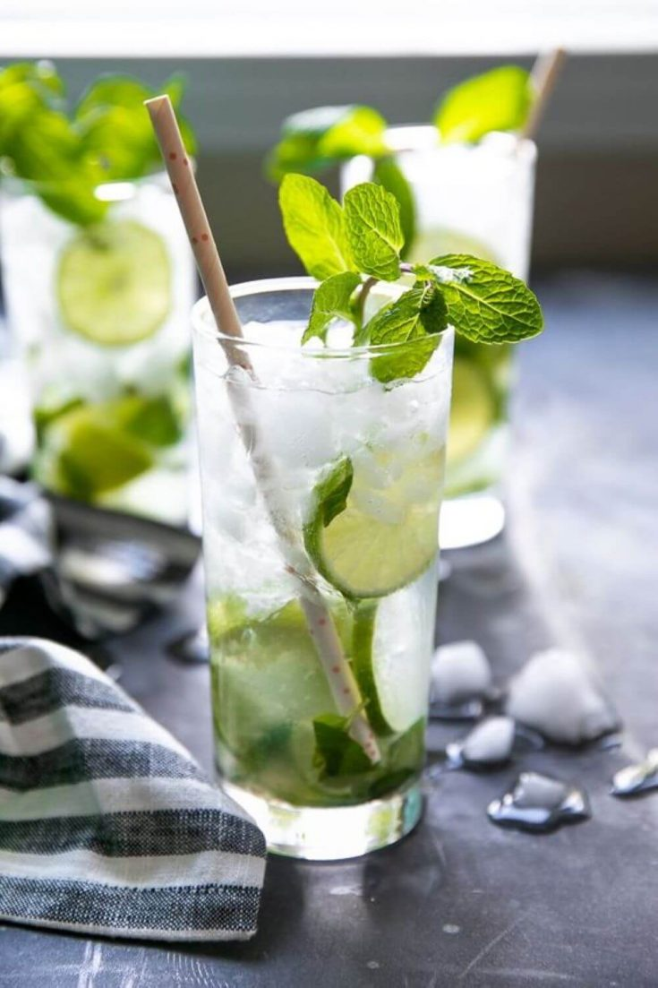 A cocktail glass of classic mojito with a paper straw in it.