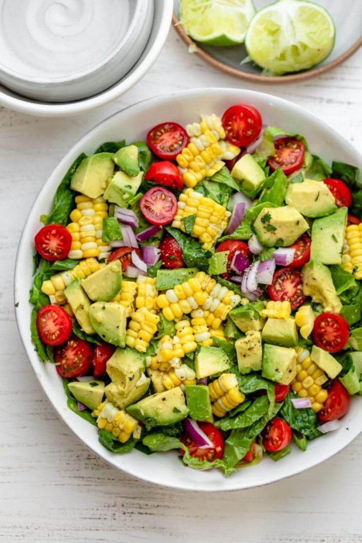 A colorful bowl of corn tomato avocado salad.
