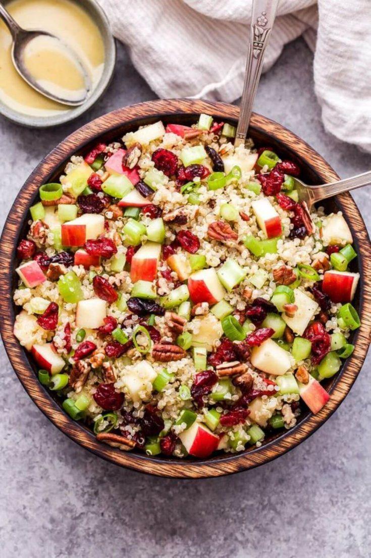 A large wooden bowl of cranberry apple quinoa salad.
