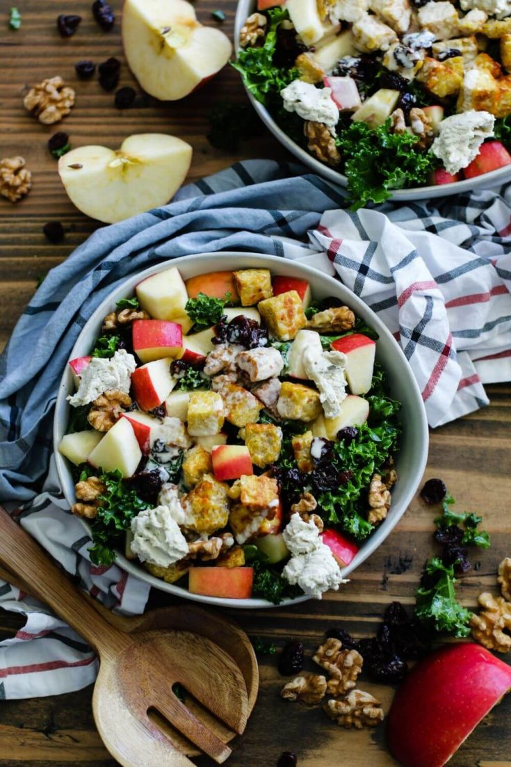 A large bowl of cranberry apple walnut kale salad with tempeh crumbles.