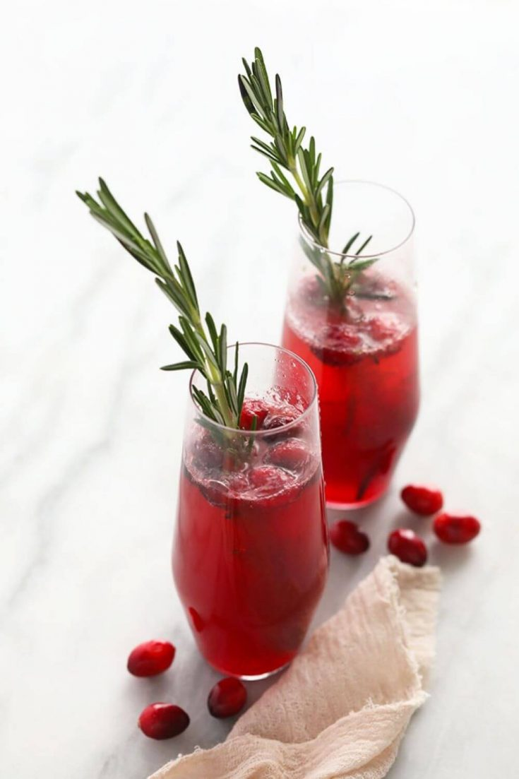 Two full glasses of cranberry mojito topped with fresh rosemary.