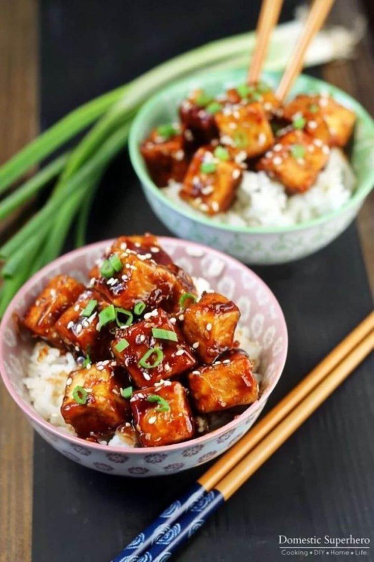 Two small bowls of crispy honey sesame tofu over rice with chopsticks.