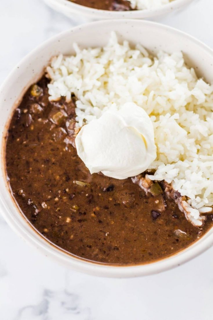 A large bowl of crock pot black bean soup with rice and a dollop of sour cream.