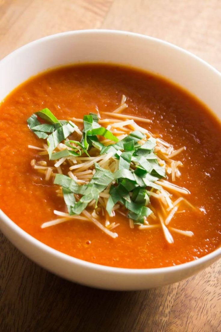 A large bowl of crock pot tomato soup topped with cheese and basil.