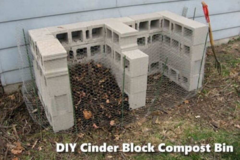 A completed diy cement block compost bin near against the side of a house.