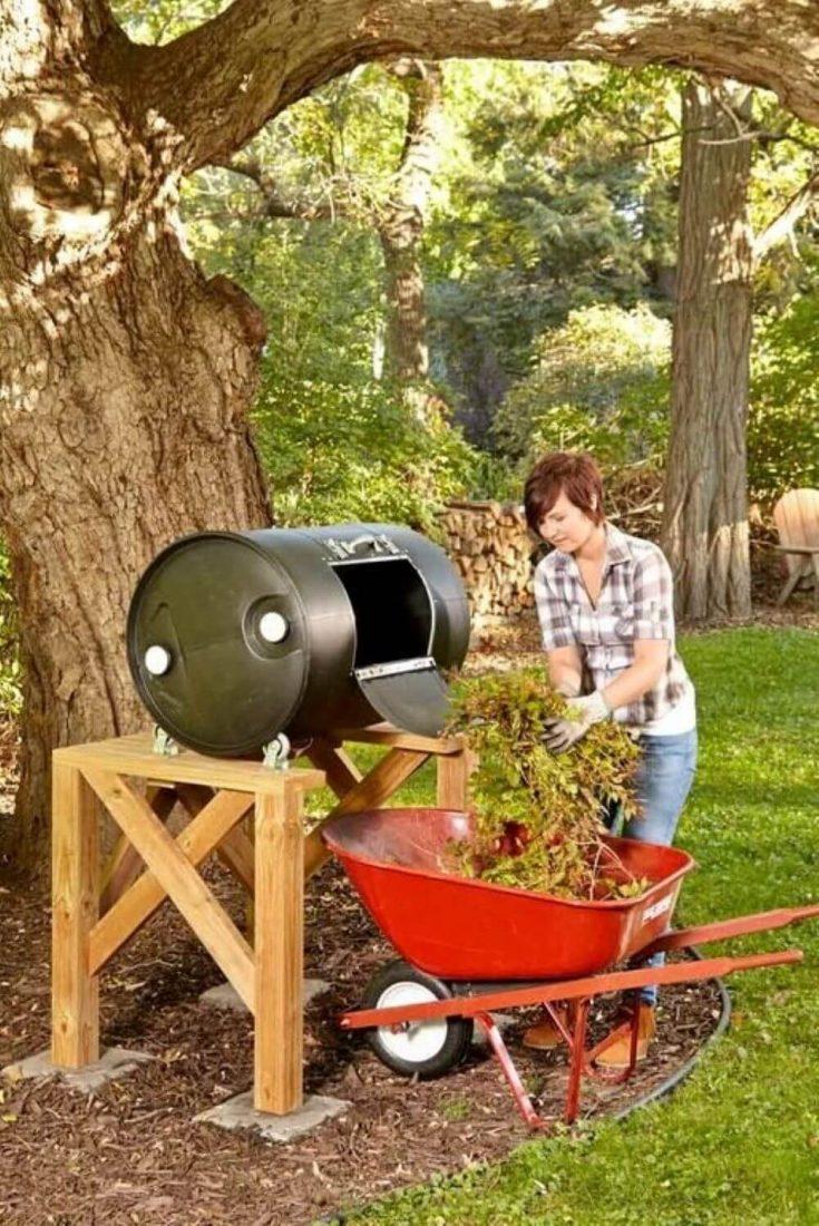A woman loading organic matter into a DIY compost barrel tumbler.