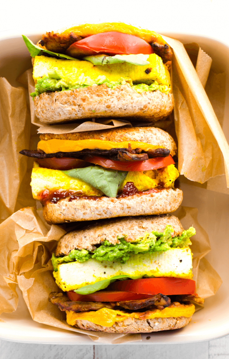 A stack of delicious vegan breakfast sandwiches with eggy tofu wrapped in brown paper.