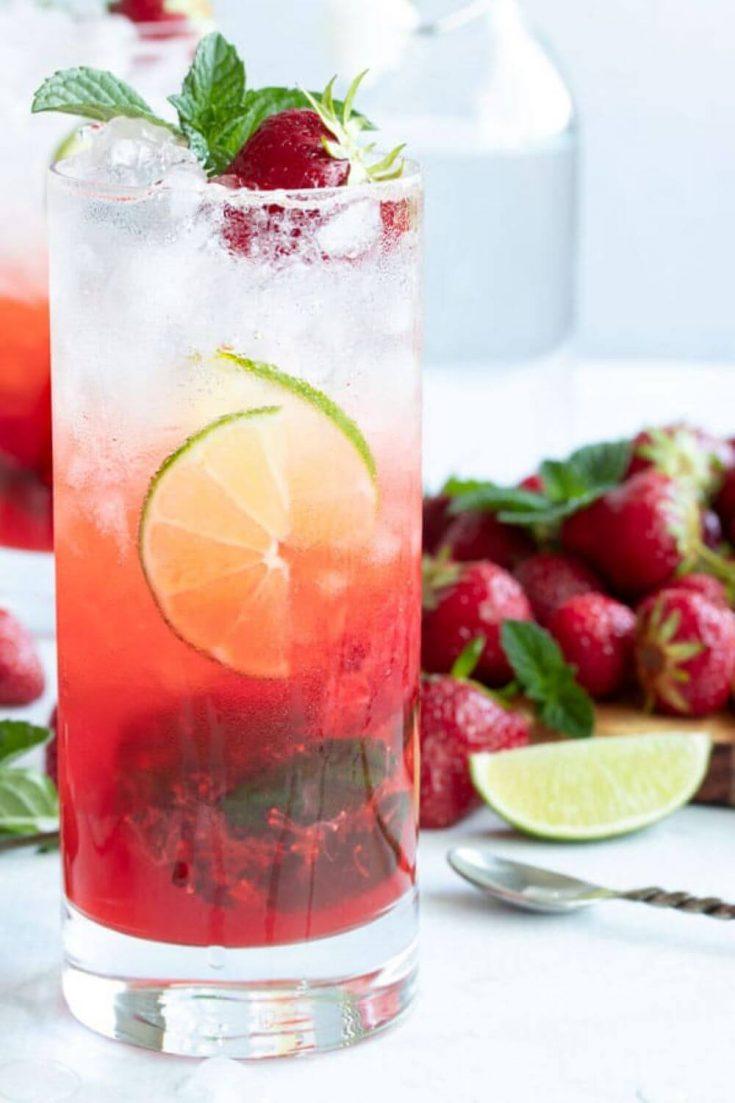 A large glass of fresh strawberry mojito.