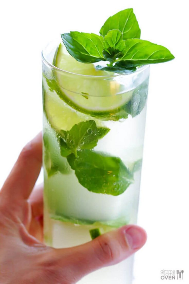 A hand holding a glass of ginger beer mojito.