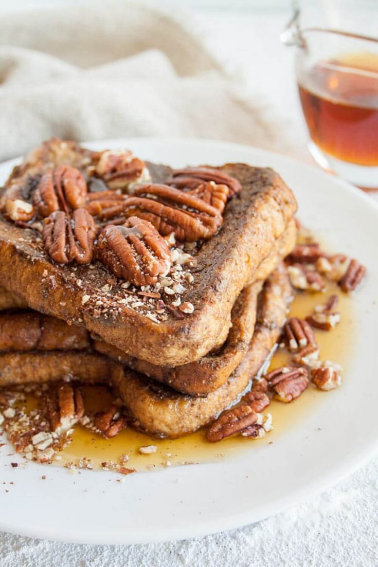 A stack of gingerbread french toast topped with syrup and pecans.