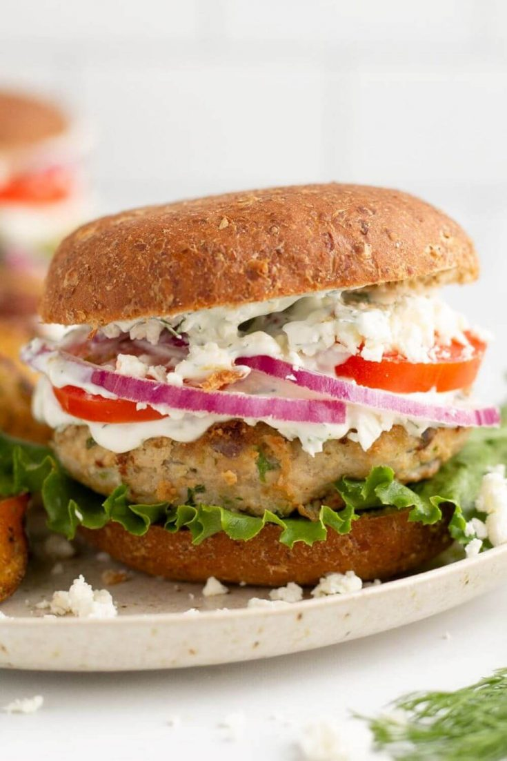 A delicious grilled Greek turkey burger loaded with tomato, onion, lettuce, and sauce all on a bun.