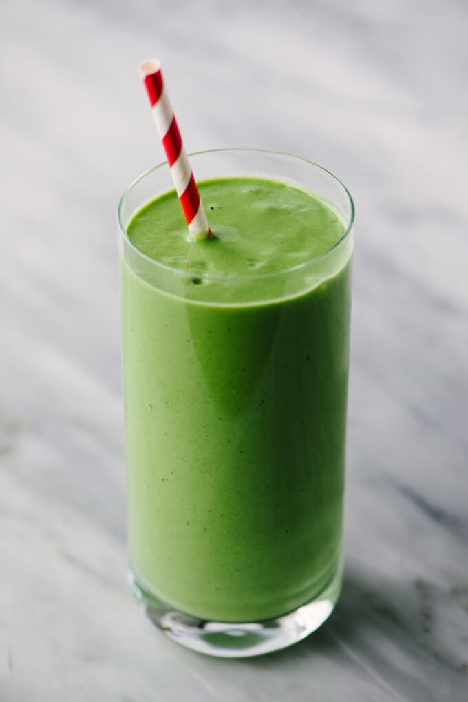A large glass of healthy mango spinach smoothie.
