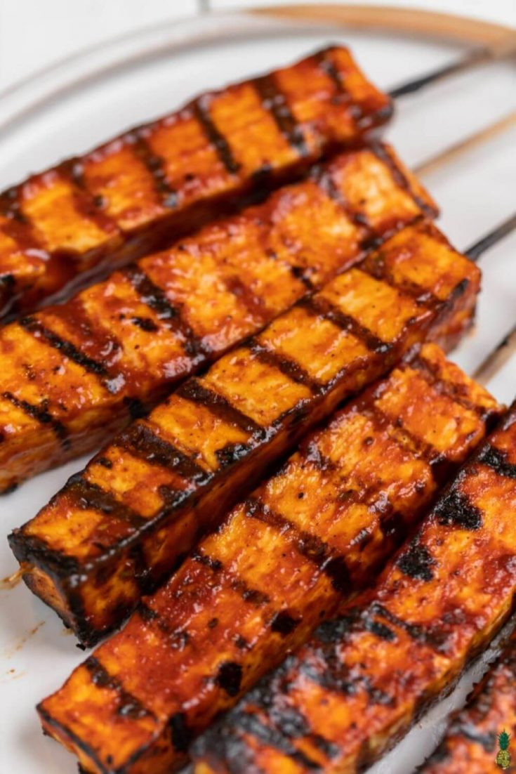 A closeup of several grilled barbecue tofu skewers.