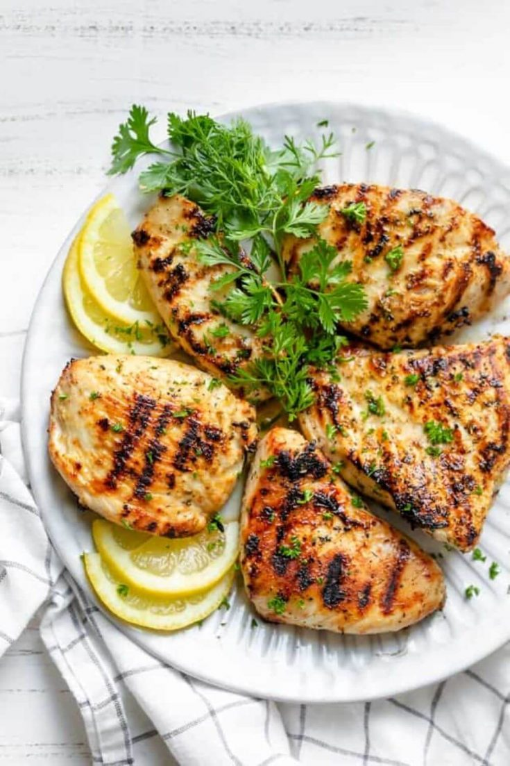 A large plate of grilled lemon chicekn topped with herbs.