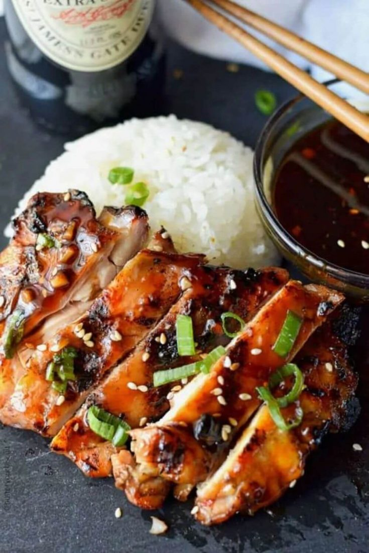 A plate of teriyaki chicken with rice and sauce.