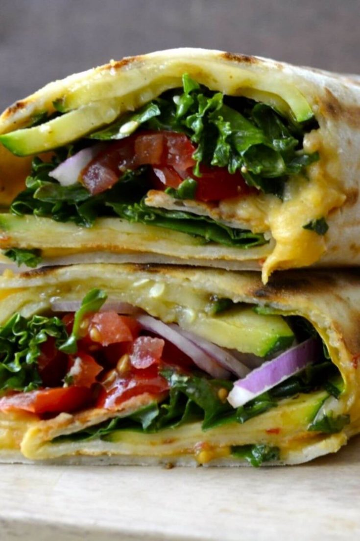 A closeup of two stack grilled zucchini hummus wraps.