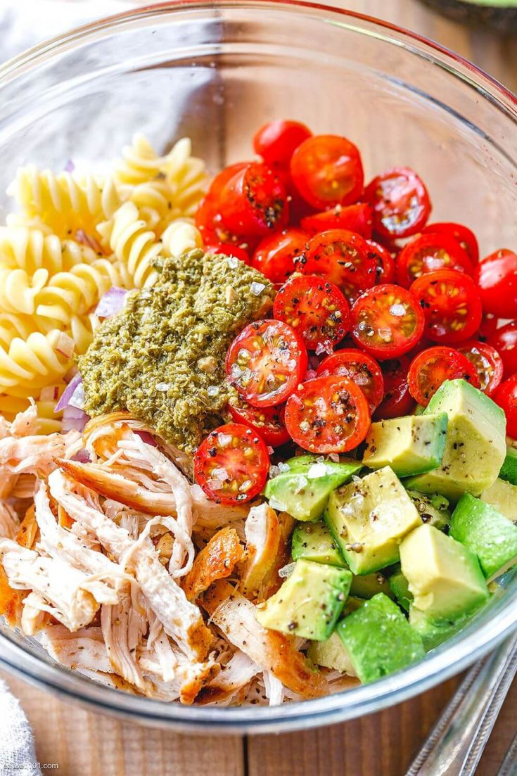 A large bowl of healthy chicken pasta salad topped with pesto, avocado, and tomato.