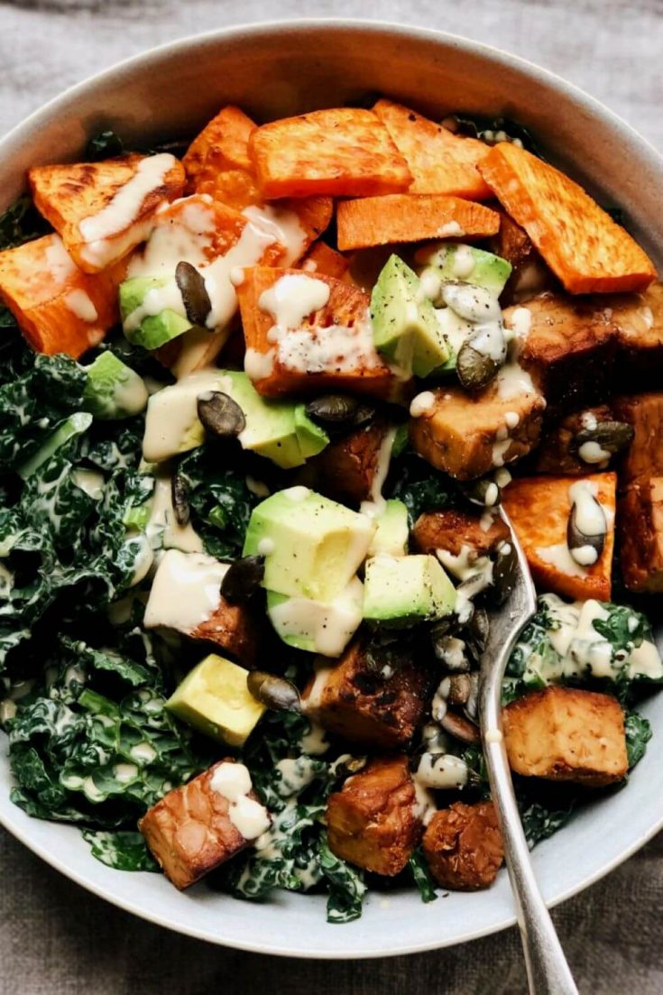 A close-up bowl of high-protein vegan kale and tempeh salad with maple tahini dressing.