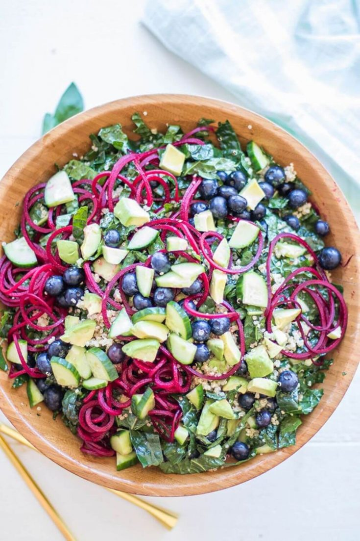 A colorful bowl of kale salad with quinoa and blueberries.