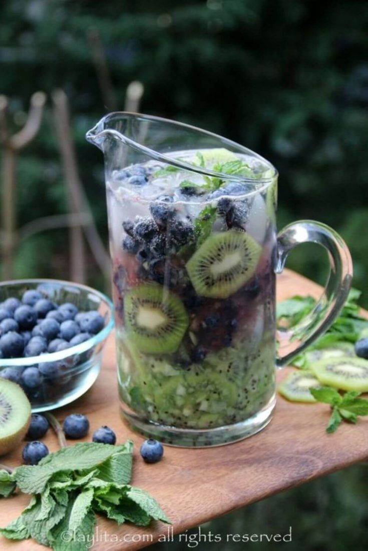 A large pitcher of fruity kiwi blueberry mojito.