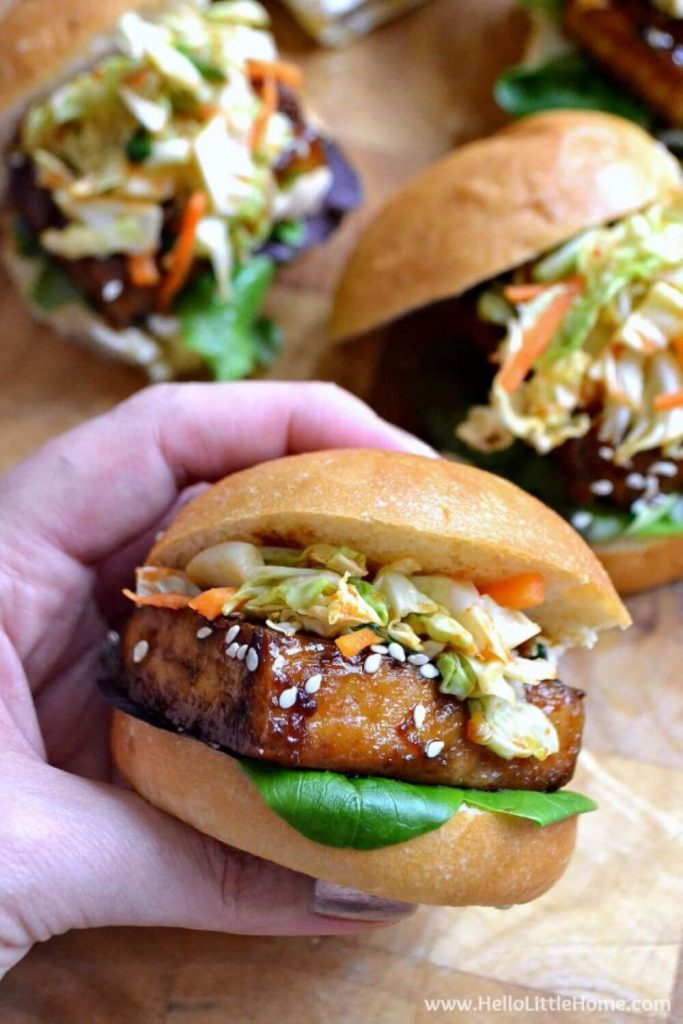 A hand holding a delicious Korean BBQ tofu slider topped with kimchi.