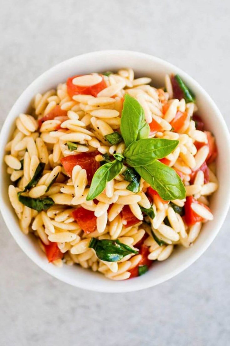 A small bowl of easy lemon orzo pasta salad topped with basil.