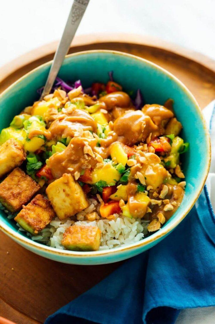 A colorful bowl of a mango burrito bowl with crispy tofu and peanut sauce.