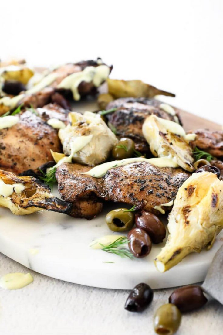 A platter of grilled Mediterranean grilled chicken with olives and artichokes.